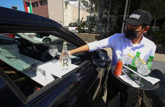 نادل يقدم الطعام للعملاء في سيارتهم خارج مطعم في الكويت