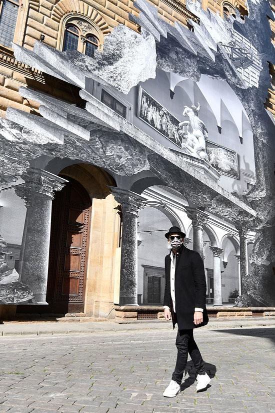 يقف الفنان الفرنسي المعاصر جي آر أمام تركيبته الفنية