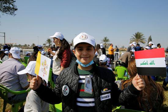صبي يحمل العلم العراقي والفاتيكان