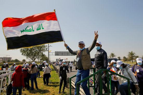 رجل يحمل العلم العراقي بينما ينتظر وصول البابا فرنسيس