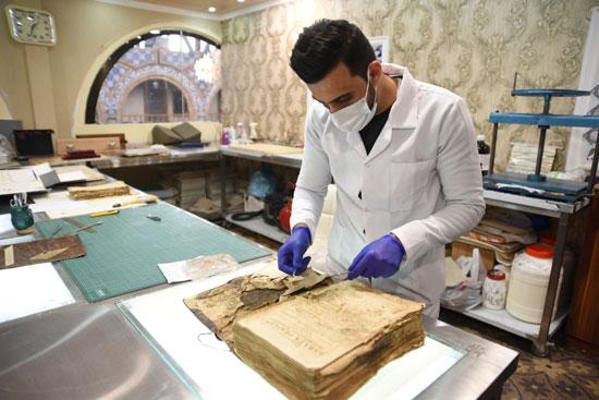 موظف يرمم مخطوطة دينية قديمة