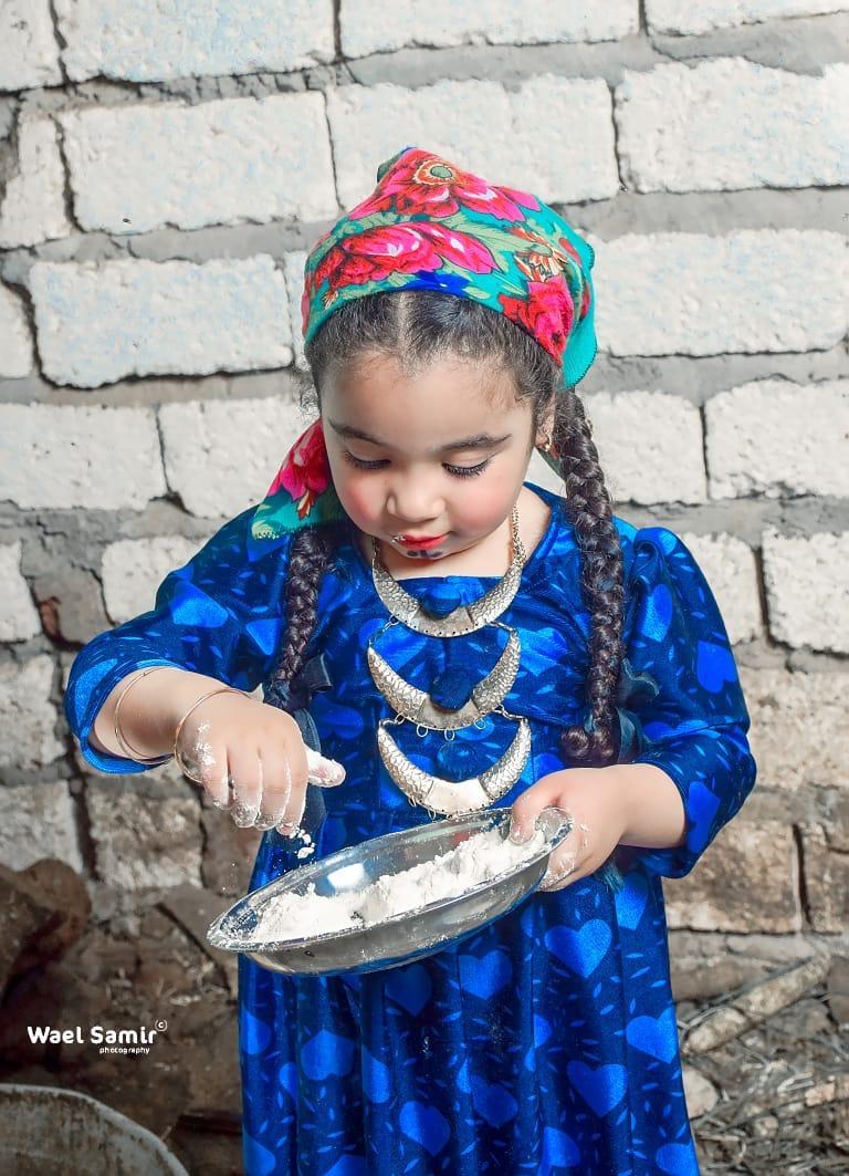 طفلة تقوم بالخبز