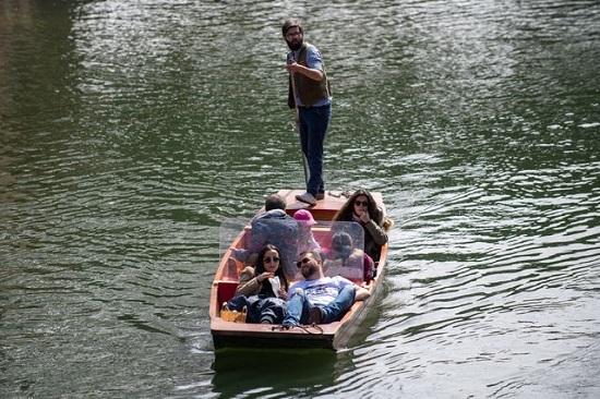 يستمتع الناس بجولة في القارب على طول نهر كام في كامبريدج
