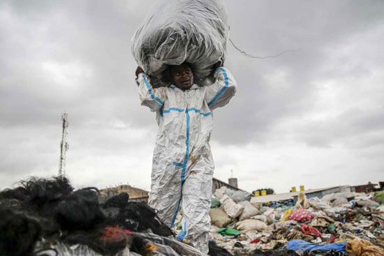 رجل يرتدي بدلة واقية وجدها في القمامة ينظف الشعر الاصطناعي في داندورا