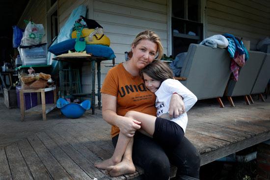أم وابنتها في شرفة منزلهما المتضرر من الفيضانات