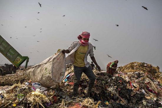 يبحث عمال القمامة عن المواد القابلة لإعادة التدوير في مكب النفايات