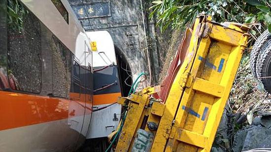 شاحنة مسطحة صفراء على جانبها بجوار القطار