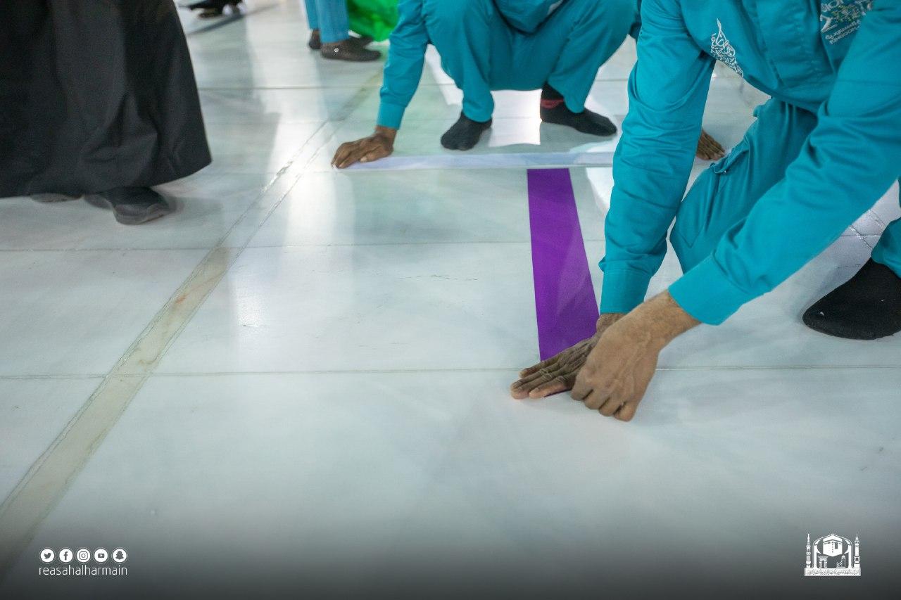 لزق اشارة على ارضية المسجد لتحديد مسار جديد للمطاف