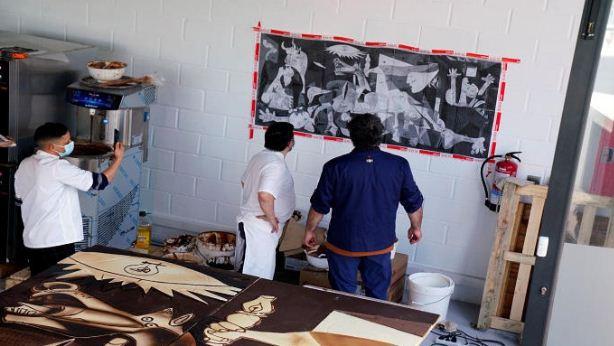 العمال ينظرون الى لوحة بيكاسو