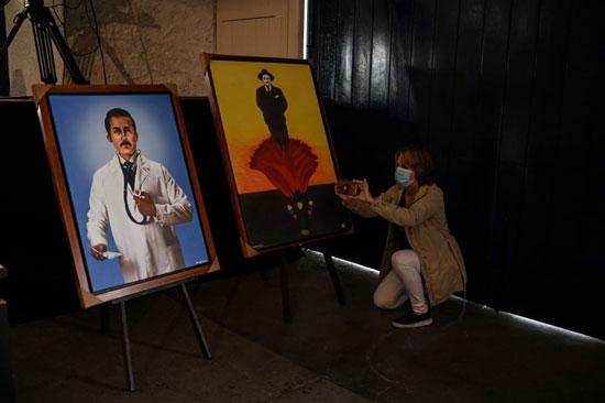 امرأة تلتقط صوراً لرسومات هيرنانديز في كنيسة