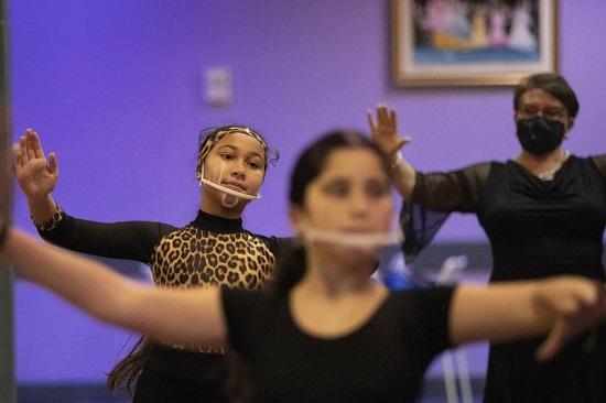 يقوم الراقصون الذين يرتدون أقنعة للحد من انتشار كورونا بالاحماء