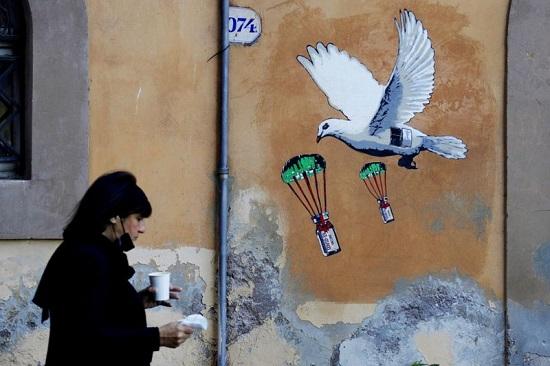 لوحة جدارية تصور حمامة بيضاء تقفز بالمظلة في زجاجات لقاح كورونا