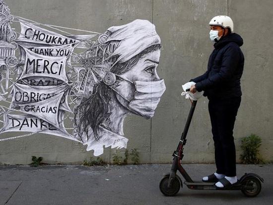 رجل يركب دراجة بخارية كهربائية أمام لوحة جدارية لفنان الشارع أرديف في باريس