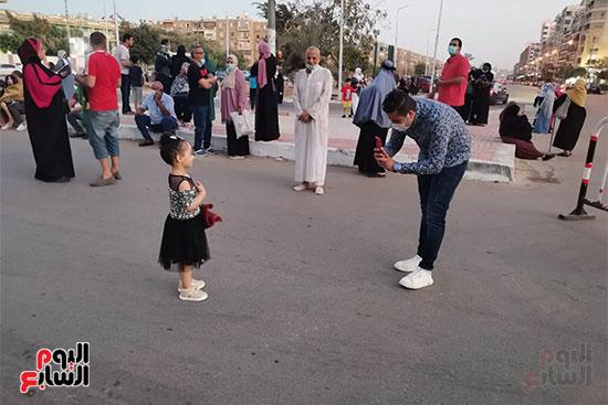 أب يلاعب ابنته بعد صلاة العيد