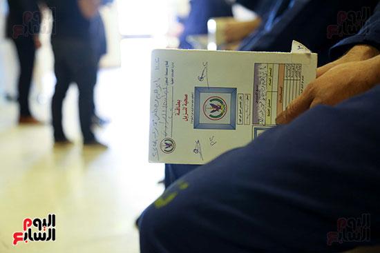 سجين يمسك بطاقة صحية