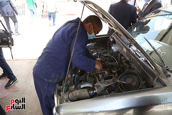 سجين يجري صيانة لسيارة داخل السجن