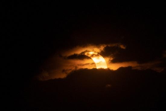 كسوف جزئي للشمس يرتفع خلف الغيوم