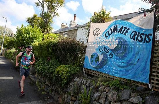 عداء يمر أمام لافتة أزمة مناخ في خليج كاربيس