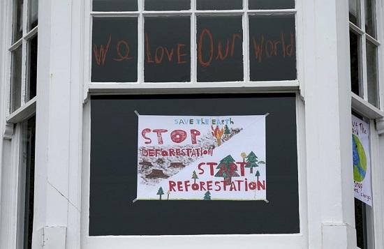 لافتة حول إزالة الغابات في نافذة منزل في سانت آيفز