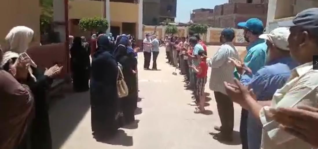 العاملون بالمدرسة يقفون صفين لتحية المدير بعد انتقاله