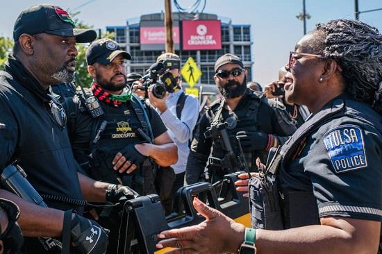يحاول ضابط شرطة نزع فتيل مواجهة بين أعضاء حزب النمر الأسود ومتظاهرين