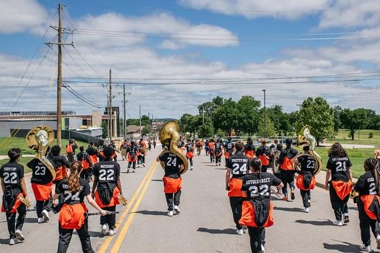 فرقة موسيقية تسير في شوارع سكنية في منطقة جرينوود خلال الاحتفالات