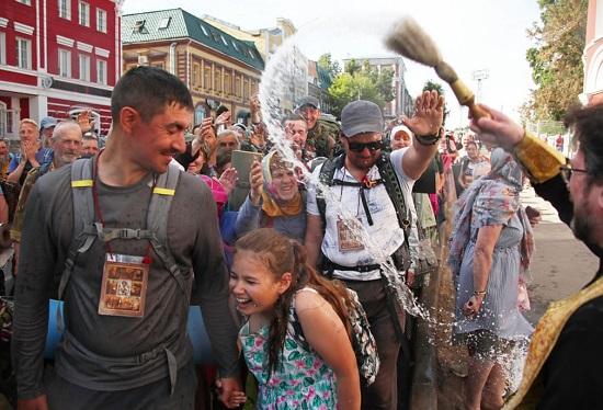 القس الروسي الأرثوذكسي يرش الحجاج بالماء المقدس
