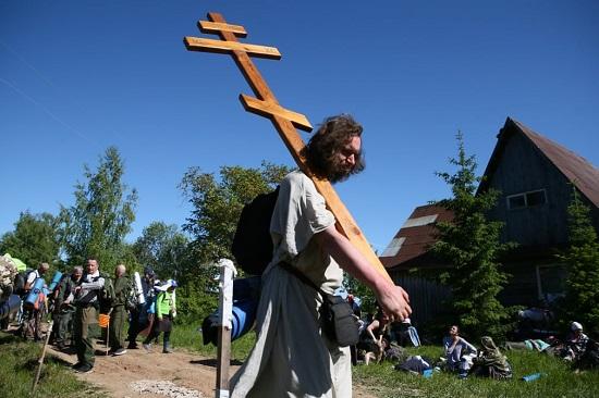 حاج يحمل صليب خشبي