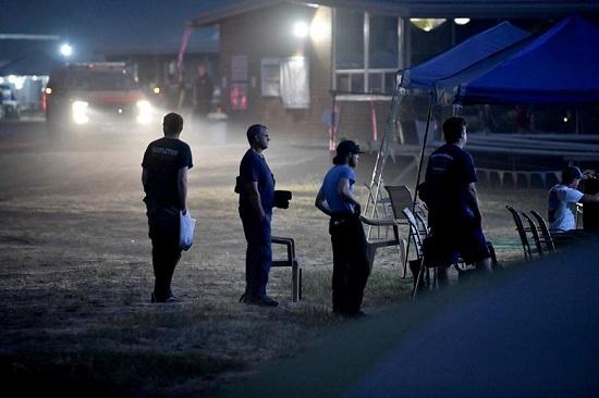 رجال الإطفاء يصطفون لاستخدام دش في معسكر لإطفاء الحرائق