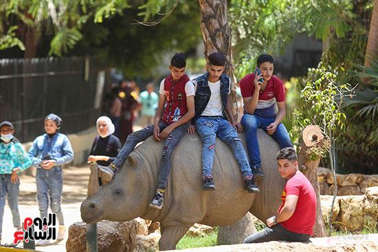 الاطفال على مجسم وحيد القرن