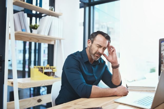 male-head-pan-ache-work-stress-laptop-desk