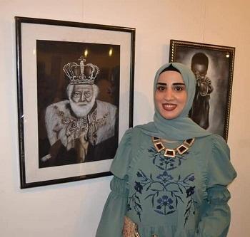 Rahma next to her paintings