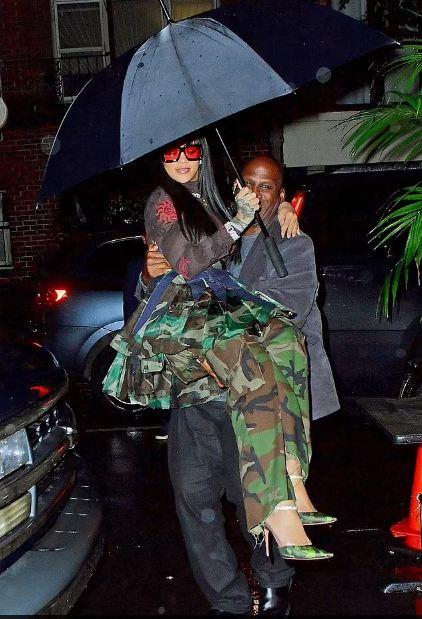 Rihanna's bodyguard carries her under the umbrella