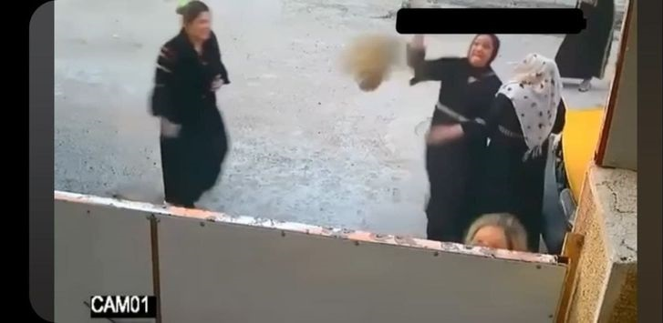 Women throw stones at the house