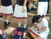 طالبة تقوم بعمل الواجب وسط التظاهرات
