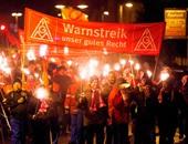 عمال يرفعون النيران أثناء مسيرتهم