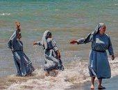 مجموعة من الراهبات يلهون على شاطئ