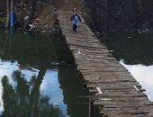 أطفال عزبة الشهاوية يعبرون الجسر الخشى