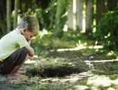 طفل حزين أمام قبر حيوان أليف