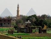 صورة توضح أهرامات الجيزة وبينهم مأذنة وسط الريف المصرى