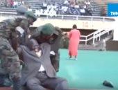 وزير الرياضة الأوغندى أثناء سقوطه على الأرض بعد ركل الكرة