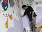 مدير المدرسة خلال دهانه للحوائط