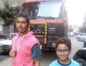 الطفلين الشقيقين امام سيارة الحماية المدنية