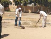 أعضاء هيئة التدريس أثناء تنظيفهم فناء المدرسة