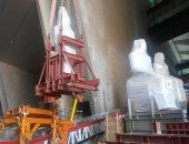تثبيت وإضاءة القطع الأثرية الثقيلة على الدرج العظيم بالمتحف المصري الكبير