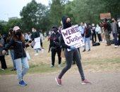 متظاهرة تحمل لافتة نريد العدالة