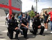 أفراد الشرطة الأمريكية يركعون أمام المتظاهرين