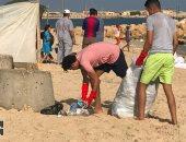 الشابان أثناء تنظيفهما شاطئ الريسة