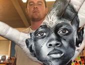 رجل يرسم رسومات بديعة على كف يده