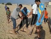 متطوعون يحفرون بئرا على الشاطئ